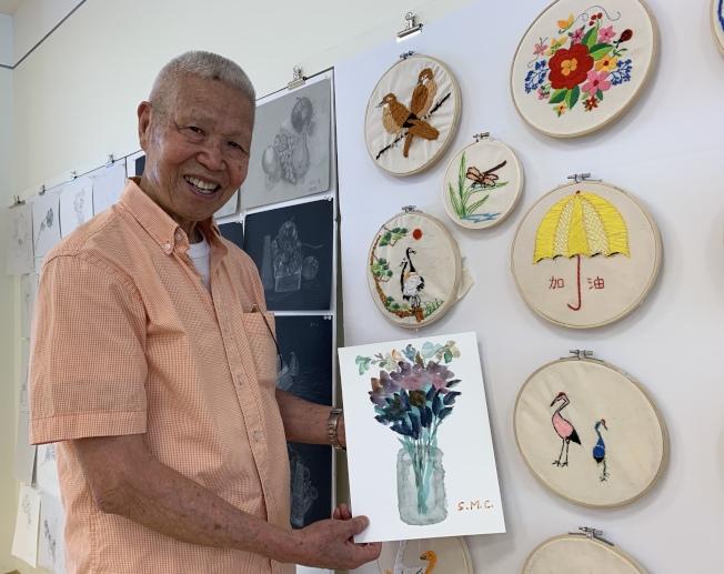 93歲的張詩明表示,色彩幫自己保持好心情,手中的水彩和右下角的兩隻小鳥刺繡都是他的作品。(記者劉大琪/攝影)