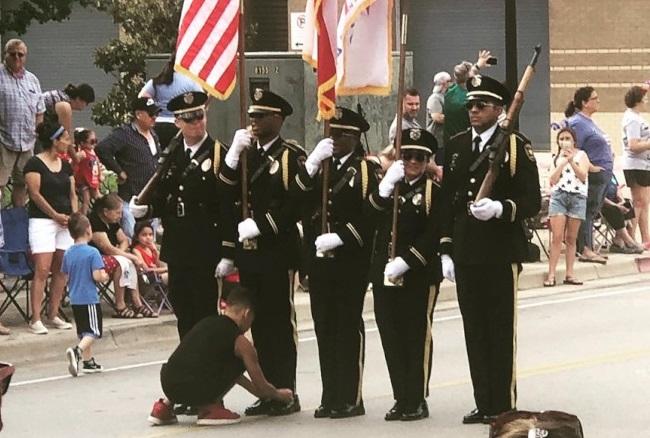 十歲小男孩喬許看到警察局儀隊的一名隊員鞋帶鬆脫,馬上到街當中幫他把鞋帶繫緊。(取自Wendy Collins Smith臉書)