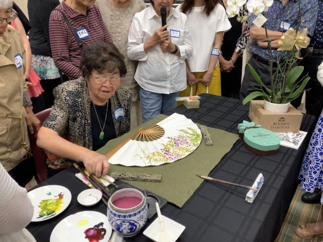 鍾維娜示範紫藤花扇面畫,並講解在扇面與宣紙上作畫的差異。(本報記者/攝影)