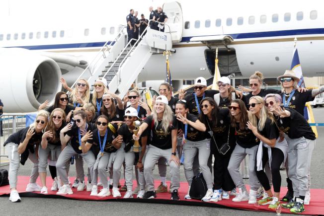 美國女足隊9日飛抵紐約,在機場接受英雄式歡迎。(美聯社)