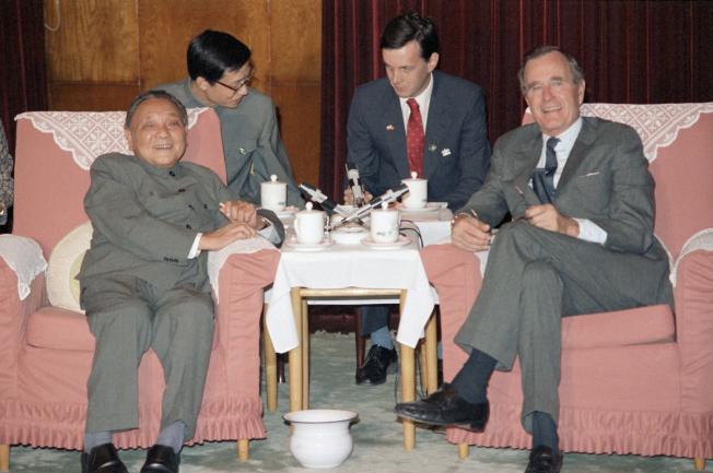 1985年10月,時任美國副總統的老布希(右)訪問北京,會見中國最高領導人鄧小平。(美聯社)