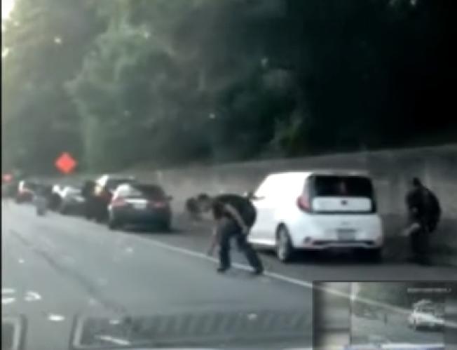 10日亞城附近I-285公路上,一輛運鈔車車門意外敞開,民眾紛紛下車撿飄揚的鈔票。(截自影片)