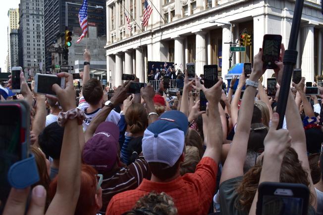 參加遊行的民眾在花車經過時,紛紛拿起手機記錄。(記者顏嘉瑩/攝影)