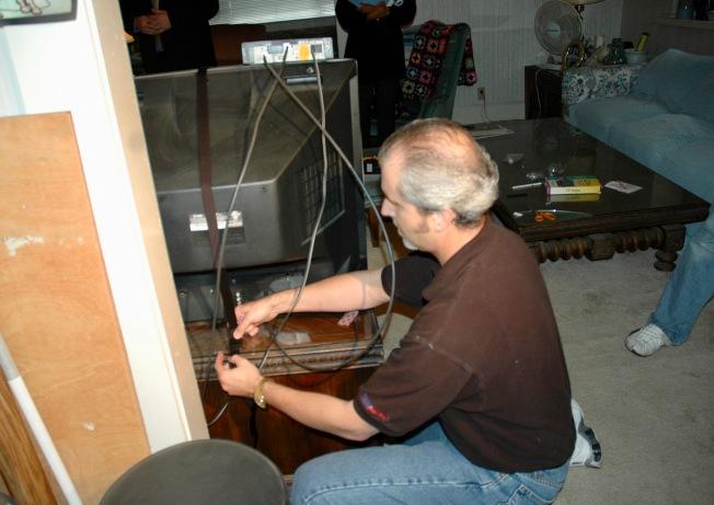 專家示範用帶子將電視機同桌子綁在一起,地震時不會翻倒。(記者丁曙/攝影)