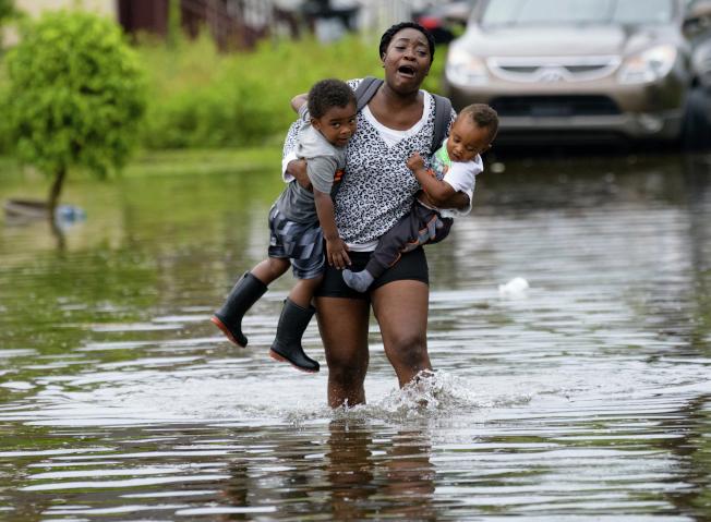 紐奧良10日遭暴風雨侵襲,一名女子抱著兩名幼童,撤離淹水地區。(美聯社)