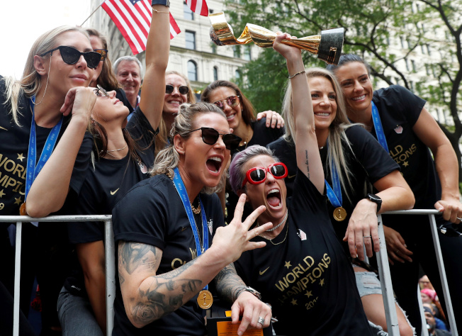 蟬聯世界杯女足賽冠軍的美國女子足球隊,10日在曼哈頓舉行勝利大遊行。圖為女足隊長拉皮諾(舉獎杯者)率女足隊員在紐約市政府接受群眾歡呼,並比出四度稱后的手勢。(路透)