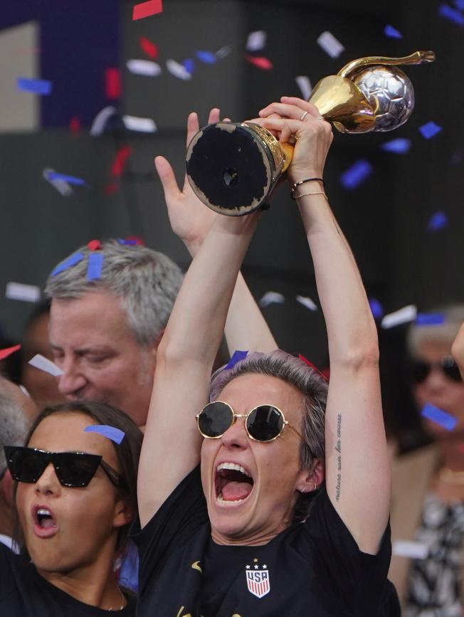 蟬聯世界杯女足賽冠軍的美國女子足球隊,10日在曼哈頓舉行勝利大遊行。圖為女足隊長拉皮諾(前)在紐約市政府舉起獎杯,接受群眾歡呼。(路透)
