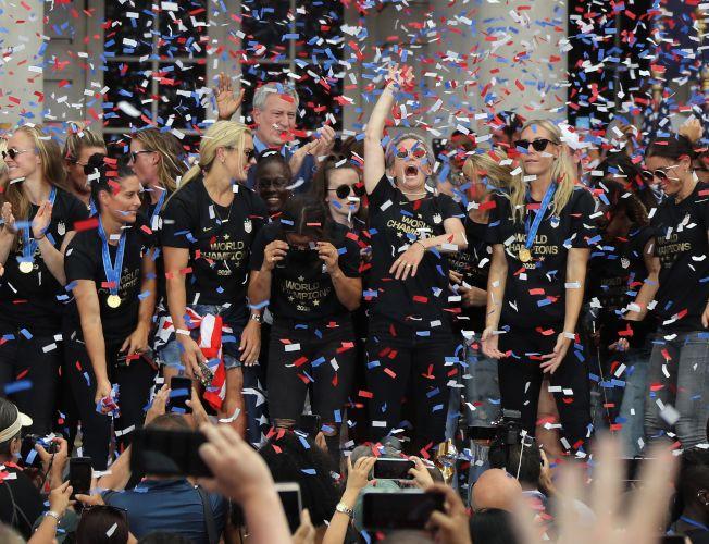 蟬聯世界杯女足賽冠軍的美國女子足球隊,10日在曼哈頓舉行勝利大遊行。圖為女足隊長拉皮諾(中)率女足隊員在紐約市政府接受群眾歡呼。(Getty Images)
