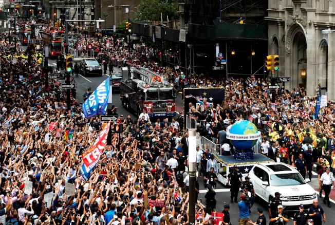 蟬聯世界杯女足賽冠軍的美國女子足球隊,10日在曼哈頓舉行勝利大遊行。圖為車隊沿曼哈頓百老匯大道前進,成千上萬群眾為女足隊員歡呼。(路透)