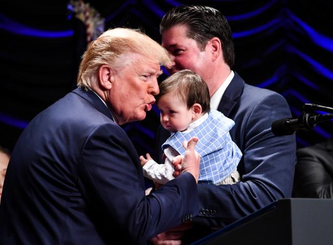 川普總統在白宮宣布改革腎臟病防治作業,簽署行政令後,抱起一名觀禮的小腎臟病患。(歐新社)