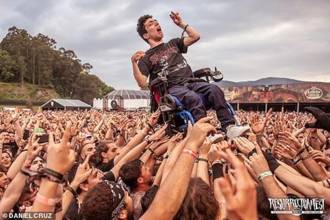 西班牙一名腦性癱瘓的19歲樂迷日前參加在比韋羅舉行的重金屬搖滾音樂祭《Resurrection Fest》,觀看瑞典樂團「邪神大敵」表演,在場群眾連人帶輪椅一起高舉過頭,讓他與大家一起擠在台下同樂,讓在場攝影師拍下被讚為年度最佳照片的影像。畫面翻攝:MAILONLINE