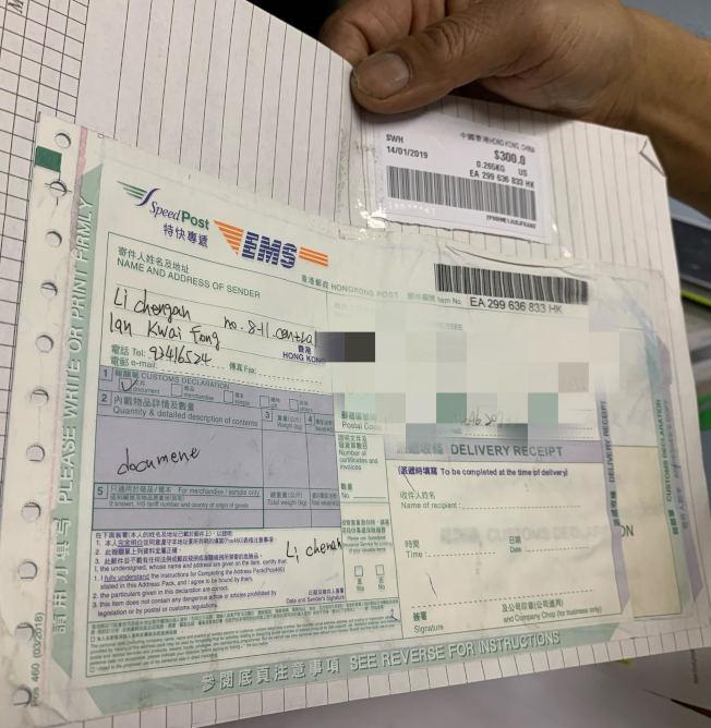 張明出示騙徒郵寄的信封。(記者牟蘭/攝影)
