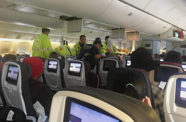 遇到亂流的加航班機迫降後,緊急醫護人員在機上治療受傷的乘客。(美聯社)