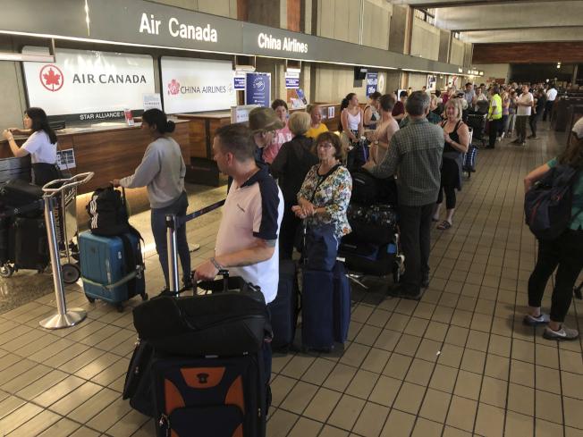 加航飛澳洲班機在夏威夷遇上亂流迫降後,該航班旅客在機場重新安排班機。(美聯社)