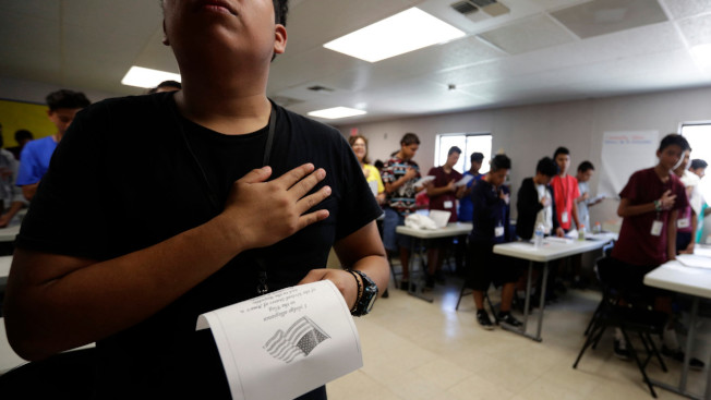 照片中的移民在德州卡瑞佐泉移民兒童收容所宣讀「效忠誓言」。 (美聯社)