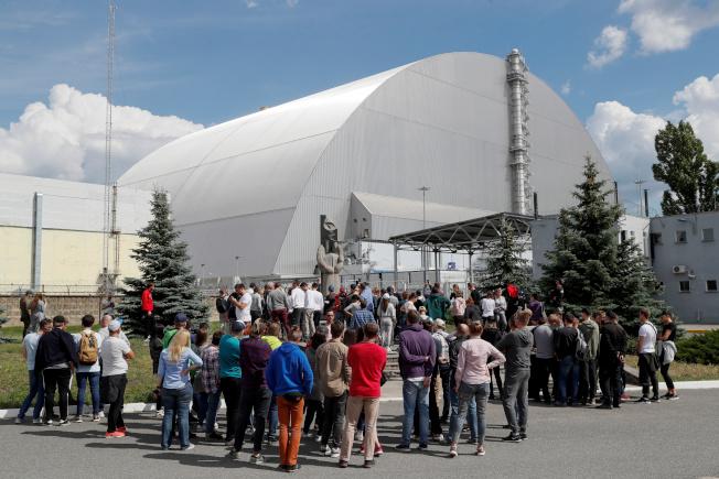 遊客們站在覆蓋車諾比受損核電站的新圍阻體外圍。(路透資料照片)