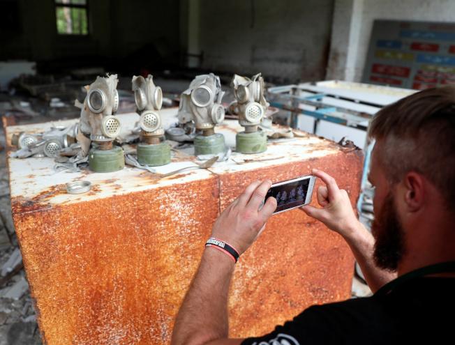 遊客在車諾比核電站附近的蘇聯軍隊前基地拍攝防毒面具的照片。(路透資料照片)