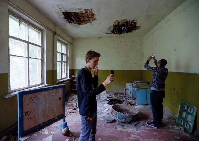 遊客在車諾比核電站附近的廢棄村莊內幼兒園拍照。(路透資料照片)