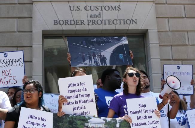 示威者舉著標語牌,在華府移民及海關執法局(ICE)總部門口,要求停止突襲抓人。(Getty Images)