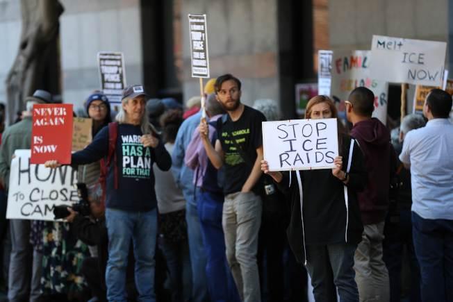 示威者舉著標語牌,在舊金山移民及海關執法局(ICE)辦公室門口,要求停止突襲抓人。(Getty Images)