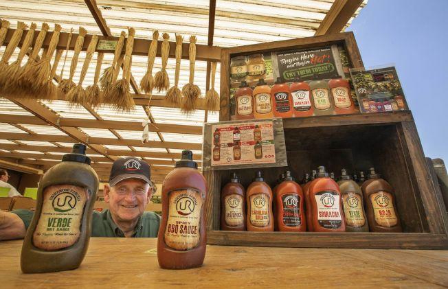 安德伍展示農場自產自銷的辣椒醬,包括一款是拉差辣椒醬(右)。(洛杉磯時報)