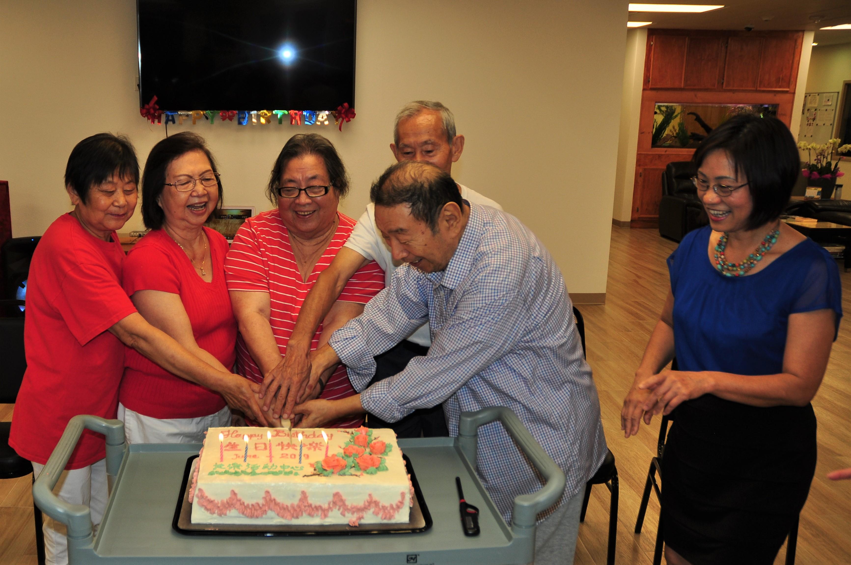 壽星開心切蛋糕。右一為長樂活動中心負責人潘小姐。