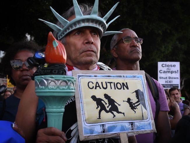 示威者在洛杉磯抗議移民及海關執法局驅逐無證移民行動,示威者並打扮成自由女神模樣,警告無證移民「小心」。(Getty Images)