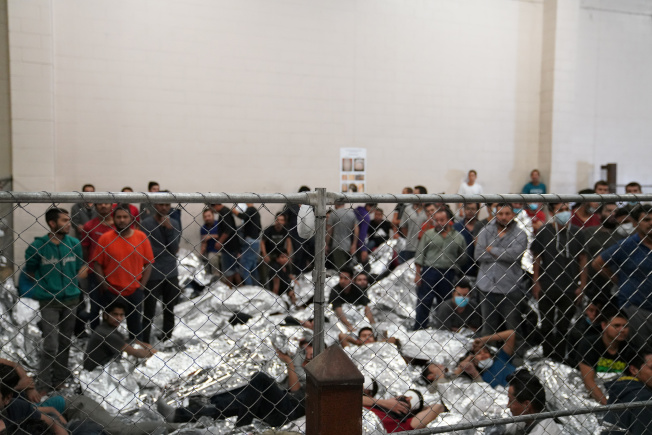 被捕的單身男性無證移民被拘押在德州麥卡倫邊界站的鐵絲網後面。(路透)