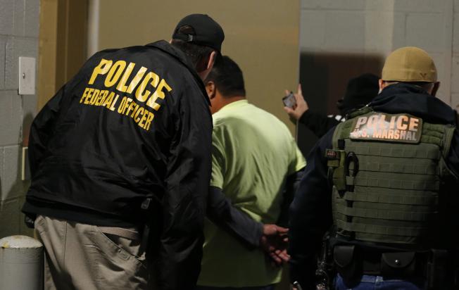 移民及海關執法局(ICE)將在周日開始驅逐無證移民,圖為ICE探員去年在維州突擊逮捕無證移民。(美聯社)