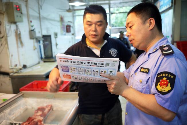 上海各執法部門聯合進行社區單位垃圾分類專項檢查,指導民眾做好分類工作。(中新社)