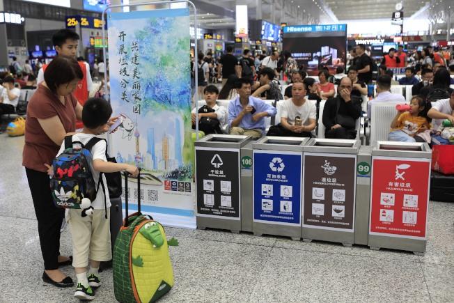 《上海市生活垃圾管理條例》上路。圖為在鐵路上海虹橋站,志願者在宣傳垃圾分類小知識。(中新社)