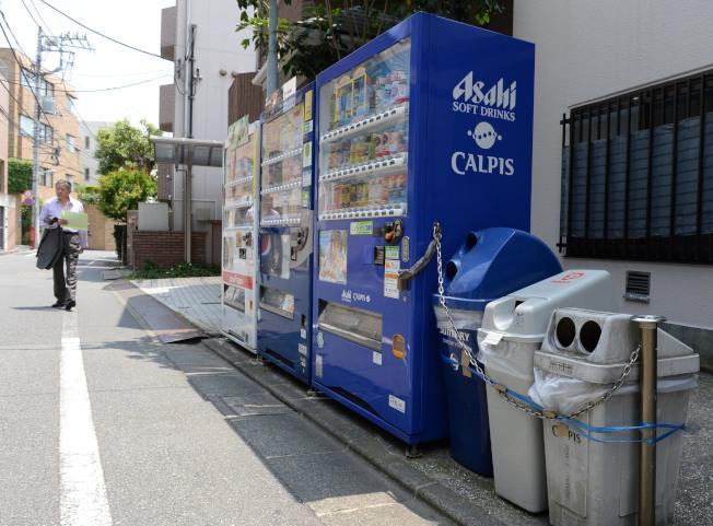 日本對垃圾分類處理十分嚴格,各類垃圾必須在規定時間放置於指定的場所。圖為東京澀谷區惠比壽三丁目自動販賣機旁的分類垃圾箱。(新華社資料照片)