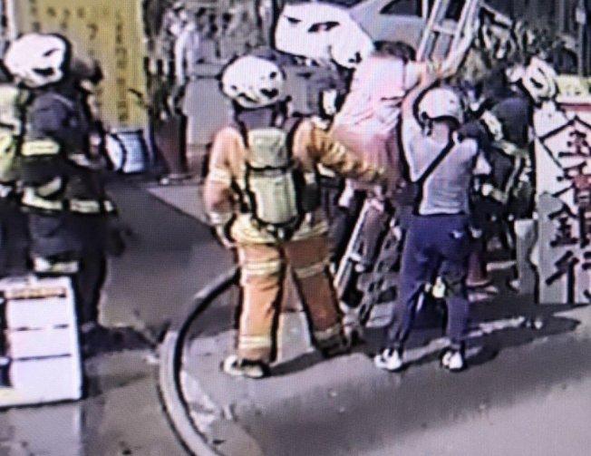 消防隊員用梯子引導大人逃生。記者鄭國樑/翻攝