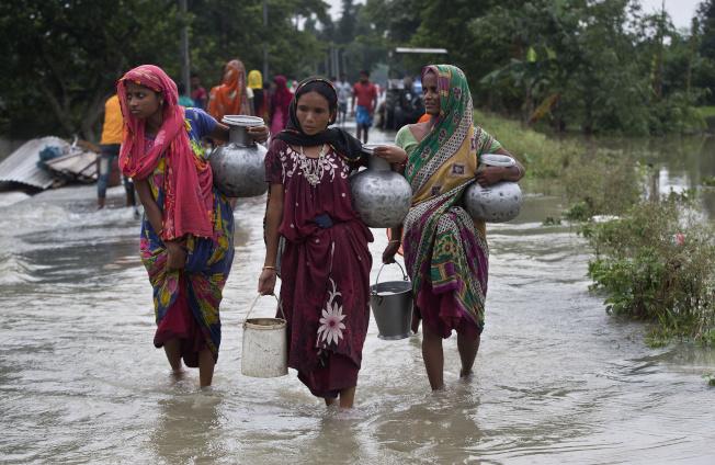 印度官員今天表示,雨季豪雨重創印度北部,一棟樓房倒塌至少壓死14人。圖為印度婦女涉水取飲用水。美聯社