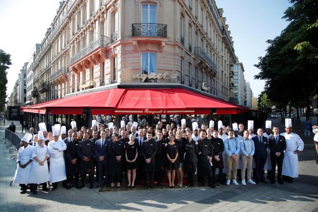 法國知名餐廳Fouquet's的員工在14日重新開張的前一天,在餐聽前合影。路透