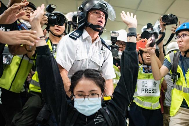 警方14日在沙田新城市廣場逐層追捕示威者時,一名女子(前)高舉雙手,證明她手無寸鐵。(Getty Images)