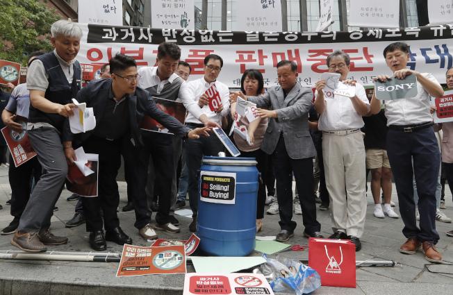 日韓貿易爭端延燒,南韓中小企業在日本大使館前撕毀日本主要企業品牌LOGO表達抗議。(美聯社)
