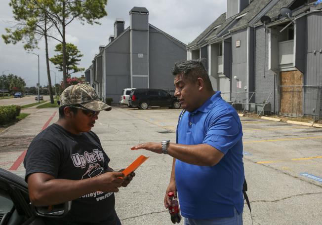 休士頓一個公寓社區15日清晨遭移民當局搜捕後,移民權益活動分子西斯內羅(右)把名為「知道你的權利」傳單發給居民。(美聯社)