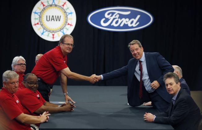 汽車工會與底特律三大車廠15日展開談判。圖為工會領袖瓊斯(左)在談判開始前,與福特汽車公司董事長比爾.福特(右)握手致意。(美聯社)