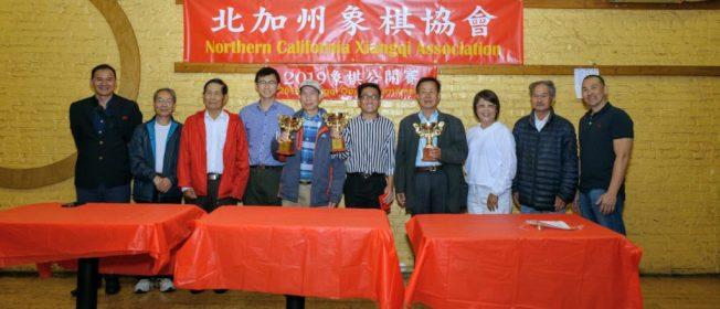 頒獎嘉賓和前三名棋手。左起:古天奇、李廣流、蘇秉湛、嚴哲鵬、吳偉元、黎英豪、余卓旋、李競芬、馮耀、余孔士。(圖片由北加州象棋會提供,Tony Cheung拍攝)