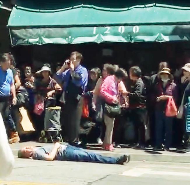 黃中華受襲墜地後立即昏迷,躺在地上,好友黃宏昶(藍衣者)上前幫忙也被攻擊。(讀者提供)