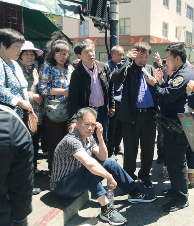 黃氏宗親會主席黃中華(坐者)被打昏迷清醒後,坐在路旁休息,同行的中華總會館中文書記黃宏昶也被嚴重打傷。(記者李秀蘭/攝影)