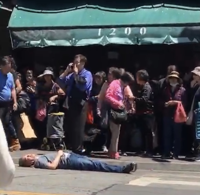 黃中華受襲墮地後立即昏迷,躺在地上,好友黃宏昶(藍衣者)上前幫忙也被攻擊。(讀者提供)