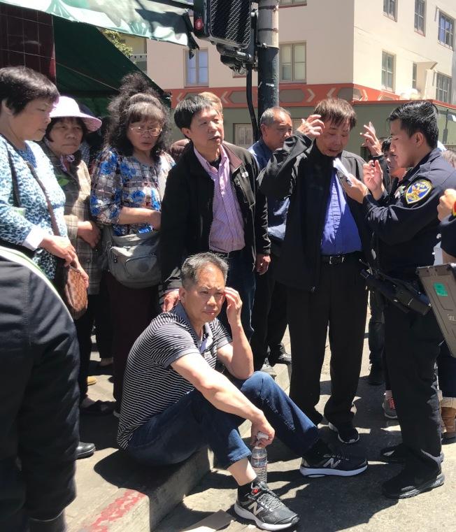 黃氏宗親會主席黃中華(坐者)被打昏迷清醒後,坐在路旁休息,同行的中華總會館中文書記黃宏昶(右二)也被嚴重打傷。(記者李秀蘭/攝影)