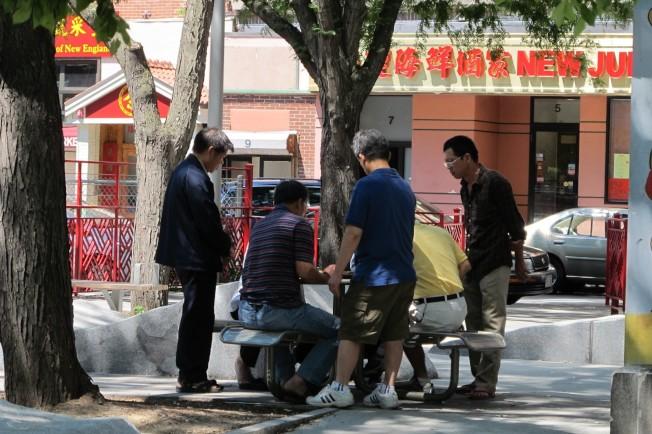 有餐館工人休工時,聚在華埠公園看人下棋。(記者唐嘉麗/攝影)