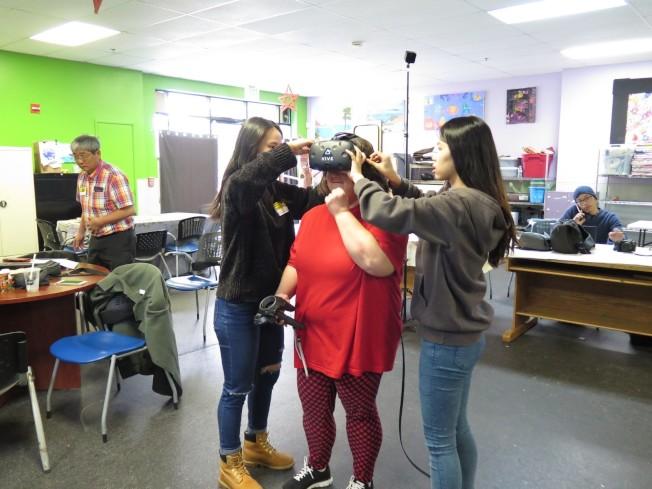 台北科技大女生請身心障礙員工實地測試使用虛擬實境。(台北科技大學管理學院網站)