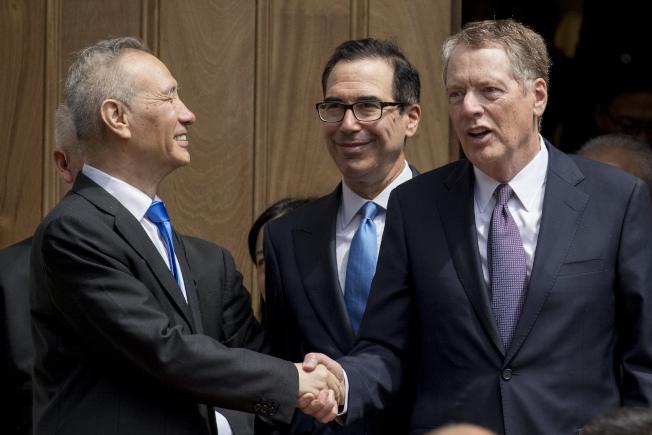 美中貿易談判路途漫長,圖為今年5月中國副總理劉鶴(左)和美國貿易代表賴海哲(右)在華府握手,中為美國財政部長米努勤。(美聯社)