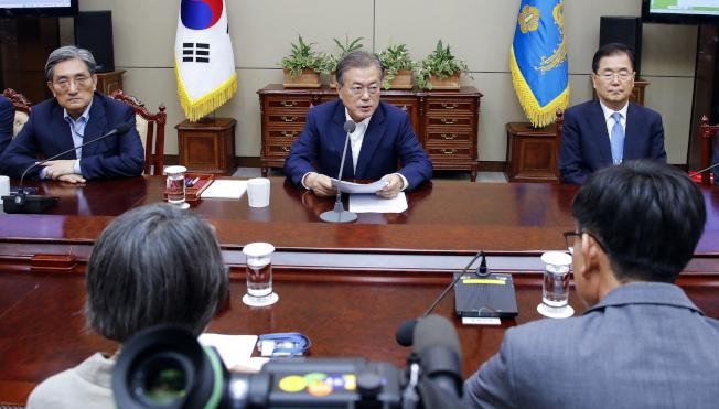 南韓總統文在寅(中)陸續與高階幕僚和產業界開會,討論如何因應日本的管制措施。(美聯社)