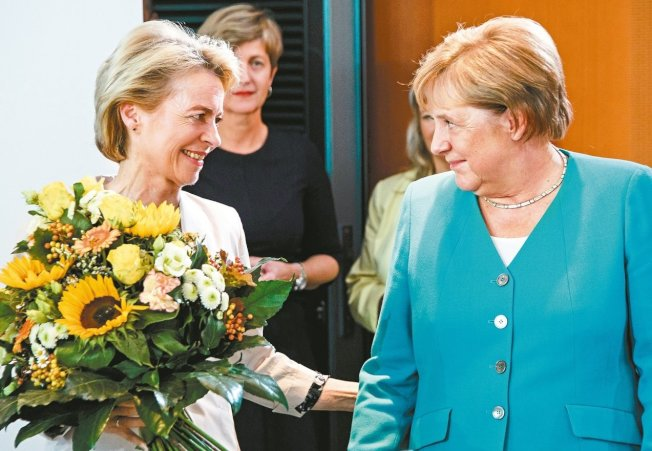 德國總理梅克爾(右)17日在柏林送花給范德賴恩(左),恭賀她將出任歐盟執委會主席。 歐新社