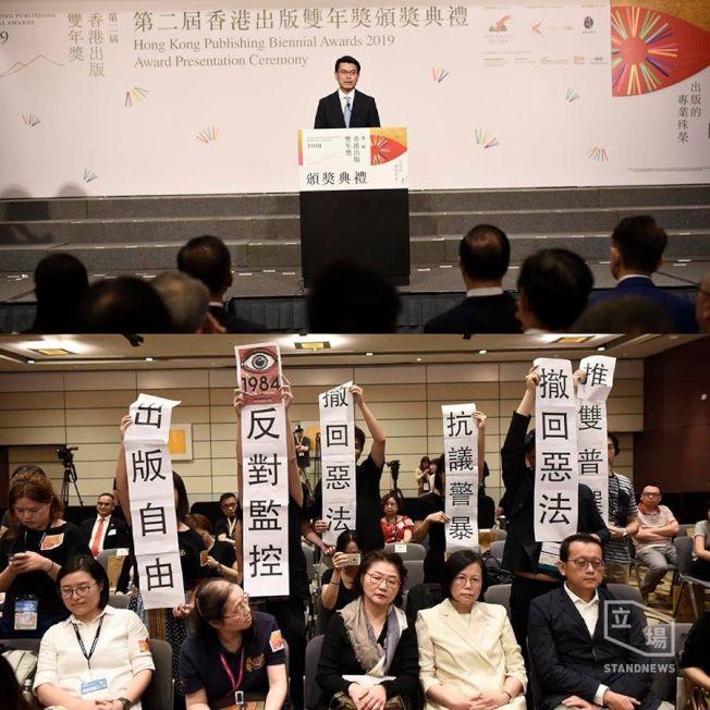 商經局長邱騰華17日出席「出版雙年獎頒獎禮」遇抗議,有與會者舉起「撤回惡法」、「抗議警暴」、「反對監控」等紙牌。(取材自立場新聞臉書)